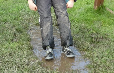 Child on swing with very muddy trousers