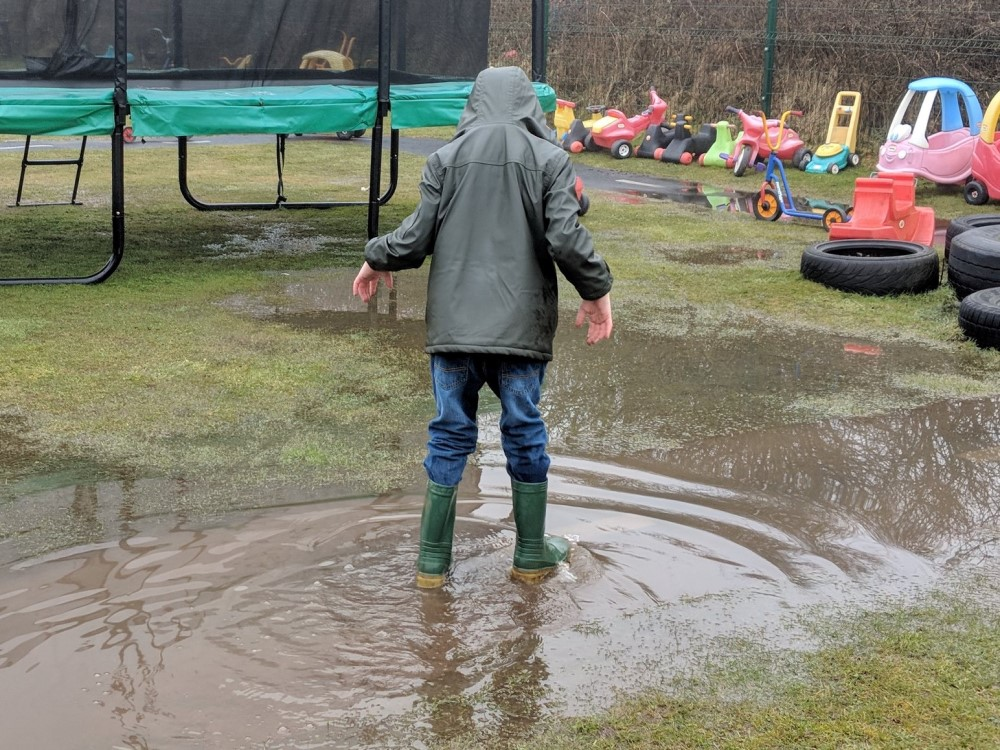 Boy playing in big puddle