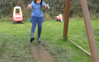 Girl on swing with muddy puddle underneath