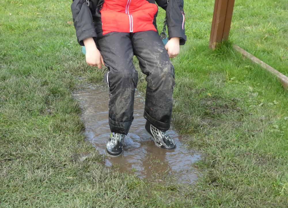 Boy on swing with muddy puddle underneath